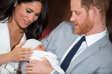 8日、英ロンドン郊外ウィンザー城で、男児を抱くヘンリー王子とメーガン妃(ゲッティ=共同)