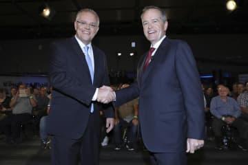 握手するオーストラリアのモリソン首相(左)と、労働党のショーテン党首=3日、オーストラリア東部ブリスベン(AP=共同)