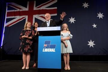 18日、オーストラリア・シドニーで、妻や娘と共に支持者に応えるモリソン首相(中央)(ゲッティ=共同)