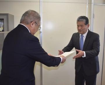 決定書を受け取る工藤氏(右)=21日午前、銚子市役所