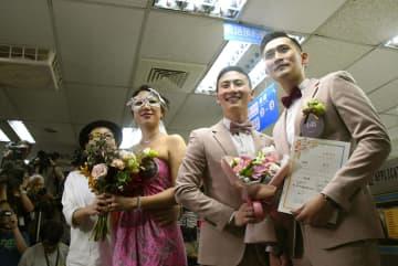 同性婚の権利を保障する特別法が施行され、台北市信義区の戸籍窓口に婚姻届の提出に訪れた同性カップルたち=24日(共同)
