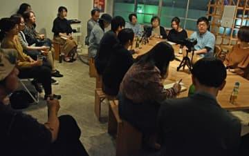 根市さん(右奥から2人目)のトークを聴く参加者ら=23日午後8時半ごろ、東京・清澄白河