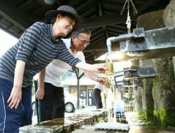 竹田市で全国初の猛暑日。冷たい湧水を求める地元の人たち=25日午後、竹田市の河宇田湧水