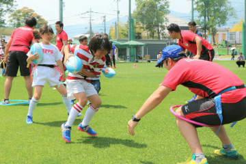 日本航空ラグビー部「JALウイングス」の選手たちとタグラグビーを楽しむ子どもたち=26日、別府市実相寺多目的グラウンド