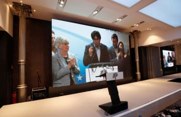 ベルギーから画面を通して欧州議会選の結果を語るスペイン北東部カタルーニャ自治州のプチデモン前首相(中央)=27日、スペイン・バルセロナ(ロイター=共同)