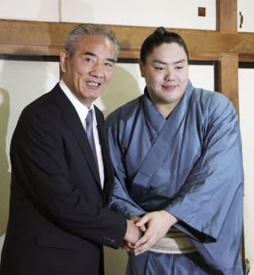 握手をする一山本(右)と師匠の二所ノ関親方=29日午前、千葉県船橋市の二所ノ関部屋