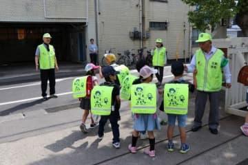 下校する児童を見守る防犯ボランティアら=30日、岡山市中区徳吉町の三勲小