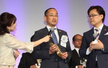 報道活動部門の大賞に選ばれ、贈賞式であいさつする山下社長室長(中央)