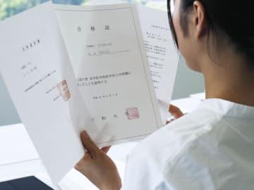 東京医科大、昭和大、順天堂大からの合格通知や謝罪の書面を見つめる原告の女性=5月(画像の一部をモザイク加工しています)