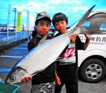 那覇一文字で95センチ、6.75キロのサバヒーを釣った饒波柚輝さん(左)=6月1日