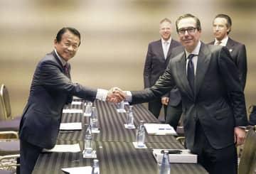 会談を前にムニューシン米財務長官(右)と握手する麻生財務相=9日午前、福岡市内のホテル