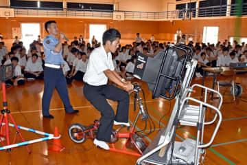 シミュレーターを使い自転車の運転マナーを学ぶ高校生=伊万里市の伊万里農林高校