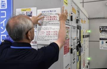 大阪駅のコインロッカーに使用中止を知らせる案内文を掲示するJR西日本の関係者=10日午前
