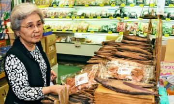松本嘉代子さんは、かつお節を扱う「松本商店」の常連客。この日の逸品を探す=5日、第一牧志公設市場周辺