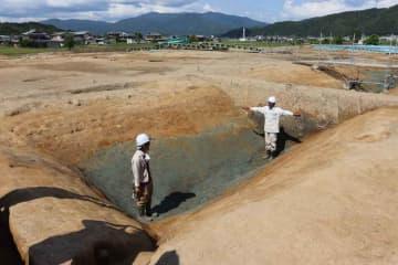 深さ最大約2メートルの堀が出土した犬飼遺跡。奥には方形居館の跡と考えられる柱穴が並んでいる(亀岡市曽我部町)