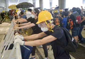 12日、立法会の敷地に乱入し、バリケードを壊そうとする若者ら=香港(共同)