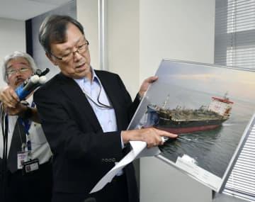 記者会見でタンカーの写真を手に説明する国華産業の堅田豊社長=14日午後、東京都千代田区