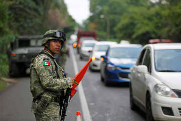 14日、メキシコ南部タパチュラの検問所で警戒する当局者(ロイター=共同)
