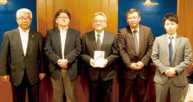 目録を受け取った国枝教育長(中央)と4LCの代表者たち