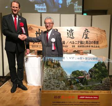 姉妹鉄道提携40周年を祝う記念品を交換し、握手する府川社長(右)とレナートCEO=湯本富士屋ホテル