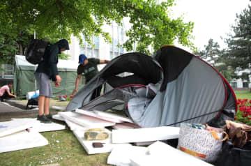 14日、モルドバの首都キシニョフの政府庁舎前でテントを片付ける民主党支持者(ロイター=共同)