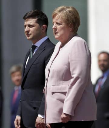 ウクライナのゼレンスキー大統領(左)の歓迎式典の際に体を震わせるドイツのメルケル首相=18日、ベルリン(AP=共同)