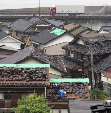 地震で多数の住宅から屋根瓦が落下する被害が出た山形県鶴岡市小岩川。雨が降りしきる中、屋根の上で撤去やビニールシートをかぶせる作業が行われていた=19日午後1時48分