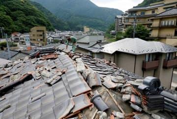 あつみ温泉街にある住宅。屋根瓦が大きく破損した=19日午前7時15分、鶴岡市湯温海