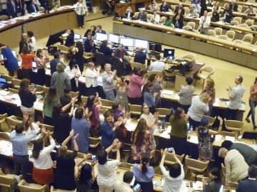 条約案と勧告案の採択を終え、喜びを分かち合うILO専門委員会の参加者ら=20日、ジュネーブ(共同)