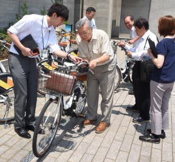 観光ボランティアガイド(中央)に対し、レンタル電動自転車の利用方法を解説する市企画課の職員(左)ら=筑西市丙