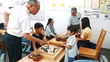 2人の先生から囲碁の打ち方を学ぶ子どもたち=諫早市、いさはや囲碁ぷらざ