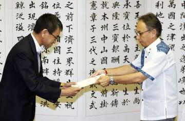 河野外相(左)と会談し、要望書を手渡す沖縄県の玉城デニー知事=22日午後、沖縄県庁