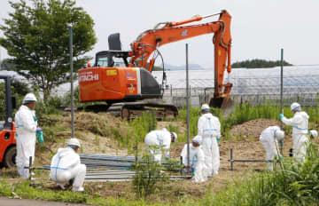 豚コレラが発生した岐阜県関市の養豚場周辺で防疫作業を進める作業員=23日午前