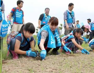 福島潟で植栽を行う中村真衣さん(手前左から2人目)ら=22日、新潟市北区