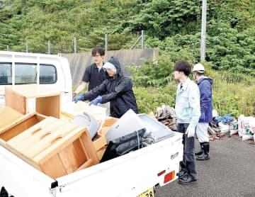 災害廃棄物を仮置き場に搬入した被災者ら=22日、鶴岡市