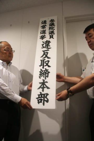 看板を設置する羽田刑事部長(左)ら=県警本部