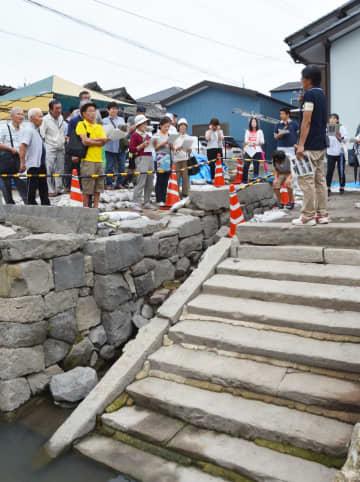 発掘現場で市職員の説明を聞く歴史ファンら=佐賀市柳町