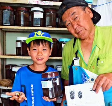 クワガタの幼虫をもらって喜ぶ長嶺小3年の古波蔵晴太さん(左)と座間味眞さん=名護市屋我