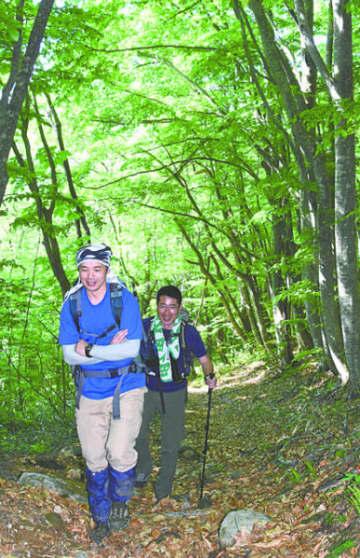 新緑に包まれた登山道を進む登山者