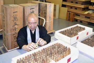 高野山で発見された木製五輪塔を手にする添田隆昭宗務総長=1日、和歌山県高野町