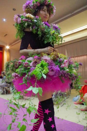 モデルの頭や胸、腰が色とりどりの花や緑のつるで飾られた=東金市