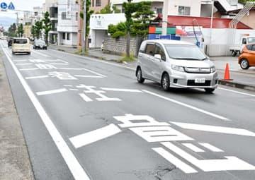横断歩道の手前でドライバーに注意を促す道路表示。速度の出やすい下り坂でも、歩行者に優しい運転が求められる=山形市七日町4丁目