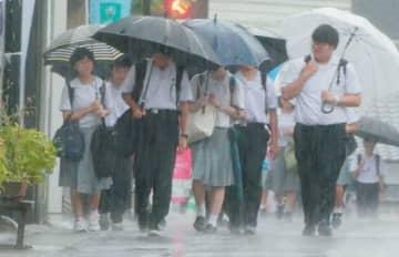 雨脚が強まる中、登校する高校生=3日午前7時20分、竹田市竹田町