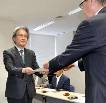 小鹿昌也局長から諮問書を受ける丸山仁会長(左)