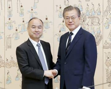 4日、ソウルの韓国大統領府での会談に先立ち、握手する文在寅大統領(右)とソフトバンクグループの孫正義会長兼社長(大統領府提供・共同)