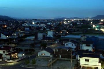 日が暮れた倉敷市真備町地区。少しずつ家に明かりが戻ってきた
