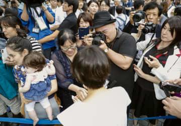 4日、街頭演説を終えた女性候補者(手前)に握手を求める有権者ら=東京都内