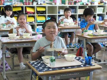 新たまねぎハンバーグを頬張る1年生=白子町立関小学校