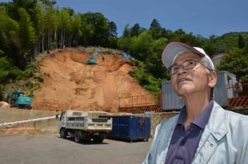 1年前の「あの日」を振り返る川端さん。トラックが止まっている更地にはかつて稲葉さん夫妻の自宅が、工事事務所が立つ場所には笹井さんの母屋と離れがあった(綾部市上杉町・施福寺集落)