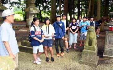 鈴木公男さん(左)から八幡神社の歴史などを聞く子どもたち
